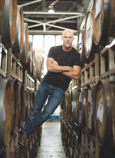 St. George Spirits master distiller Lance Winters leans against what appear to be barrels of whiskey at the distillery's barrel warehouse in Alameda, California.