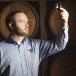 Chris Fletcher, master distiller at Jack Daniel's, inspects a glass of whiskey from the barrel warehouse.