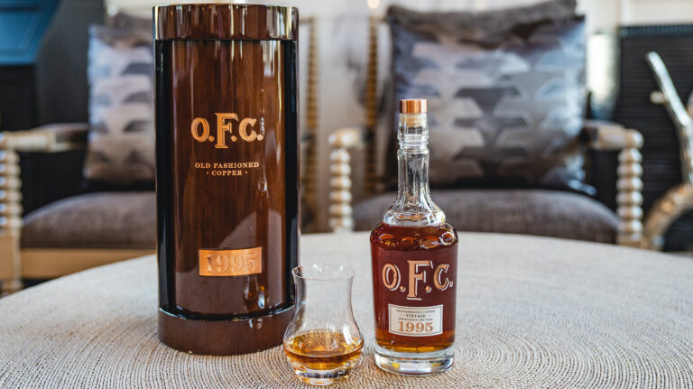 Buffalo Trace OFC 1995 bottle, canister, and a glass of bourbon on a table