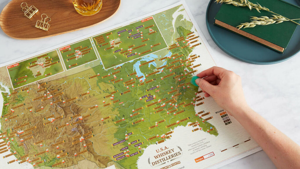 hand on a Scratch-Off USA Whiskey Distilleries Map