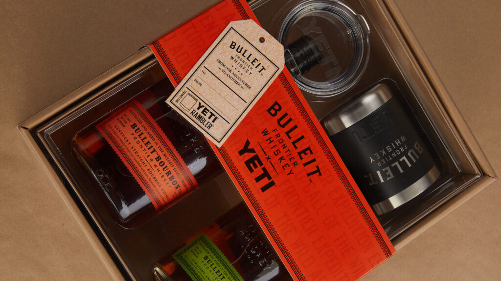 Two bottles of Bulleit whiskey in a gift box with a Yeti cup