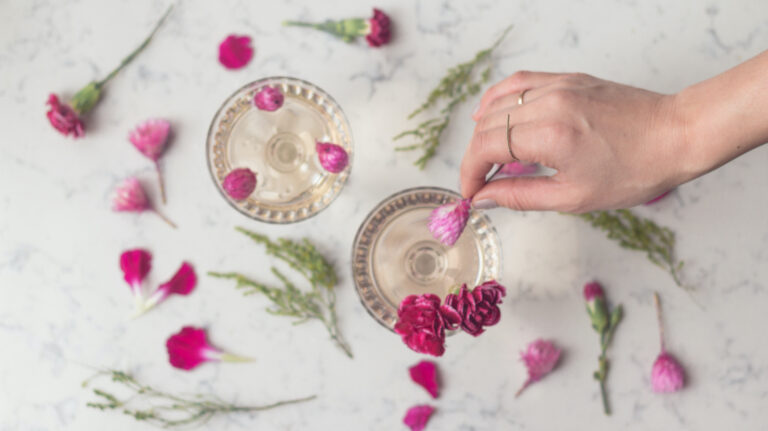 A hand places flowers as a garnish to a champagne cocktail