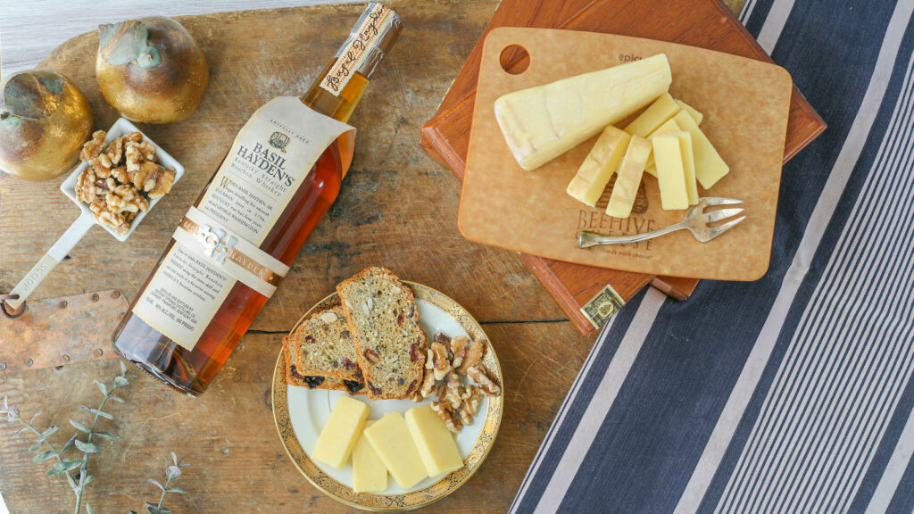 A bottle of Basil Hayden's bourbon lays next to a cheese plate and some nuts