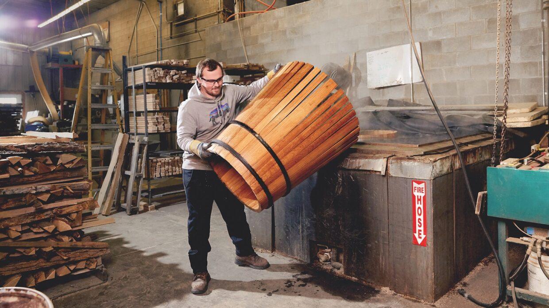 A man puts a barrel together in a cooperage