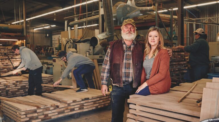 A father and daughter stand in a cooperage as workers around them make barrels