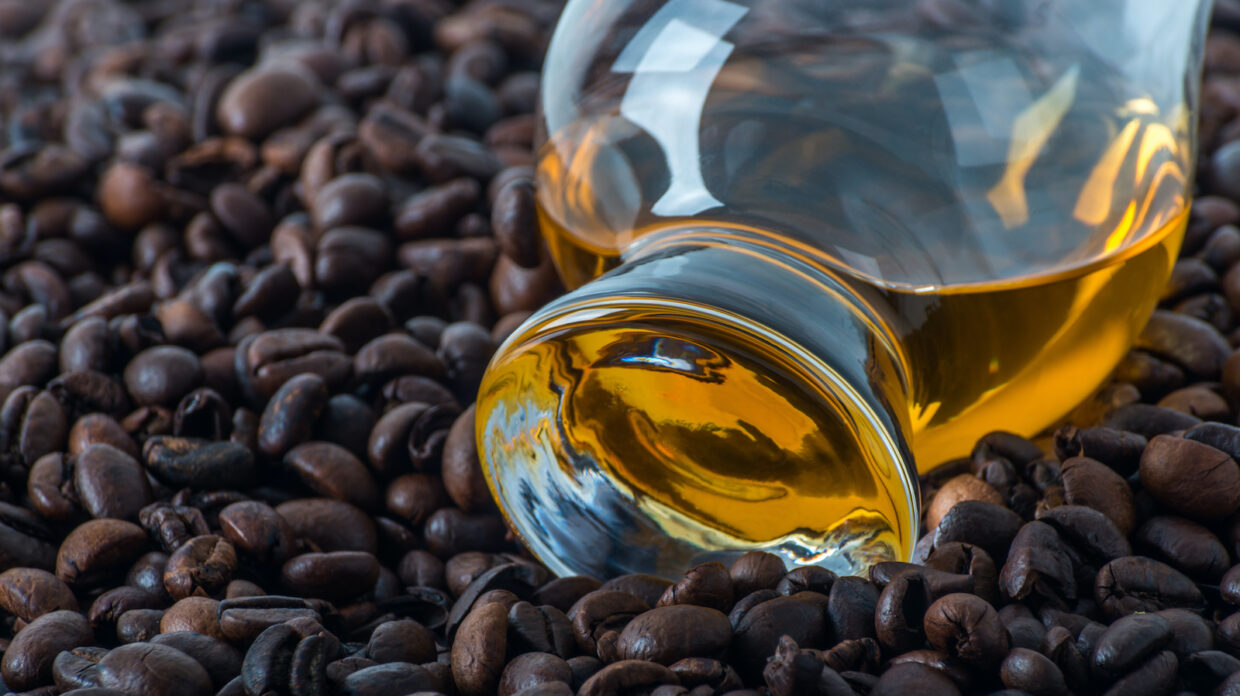 A whisky bottle sits atop coffee beans.