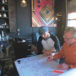 Two men sit at a desk looking over building blueprints