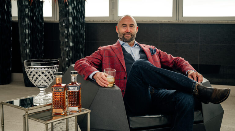 A man sits in a lounger chair holding a glass of whiskey. Two whiskey bottles sit on the table near him.