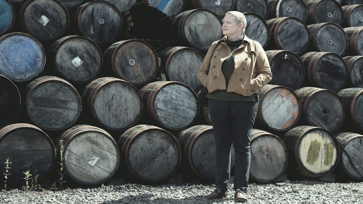 Johnnie Walker master blender Emma Walker stands in front of a wall of casks