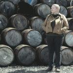 Johnnie Walker master blender Emma Walker stands in front of a wall of casks