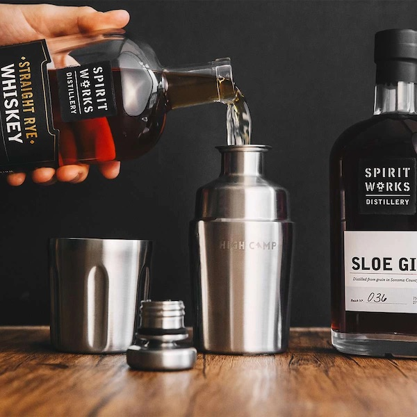 A bottle of whiskey is poured into a metal flask