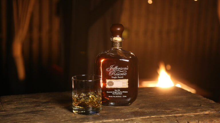 a bottle of Jefferson's Reserve Single Barrel bourbon with a glass of whiskey in front of a fire