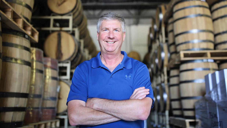 kent rabish of traverse city distillery in front of barrels