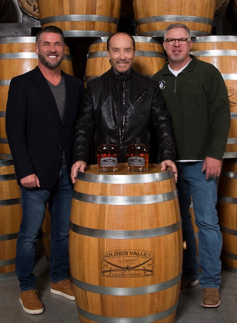 soldier valley spirits CEO david young, country star lee greenwood, and soldier valley spirits founder jeff hadden posing with a barrel and two bottles of lee greenwood signature bourbon