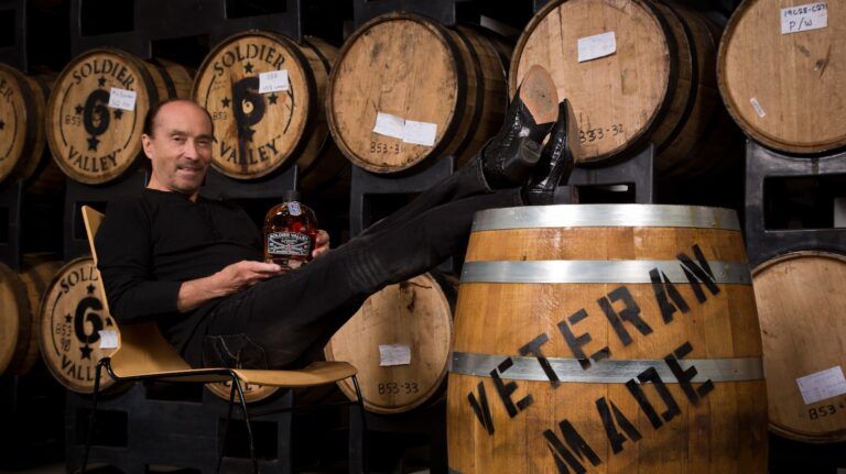 country music star lee greenwood sits with his feet on a barrel and holding a bottle of his eponymous Soldier Valley Spirits bourbon