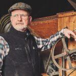 A man stands by an antique grain mill