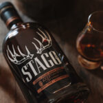 a bottle of stagg jr. bourbon with a whiskey glass and deer antler