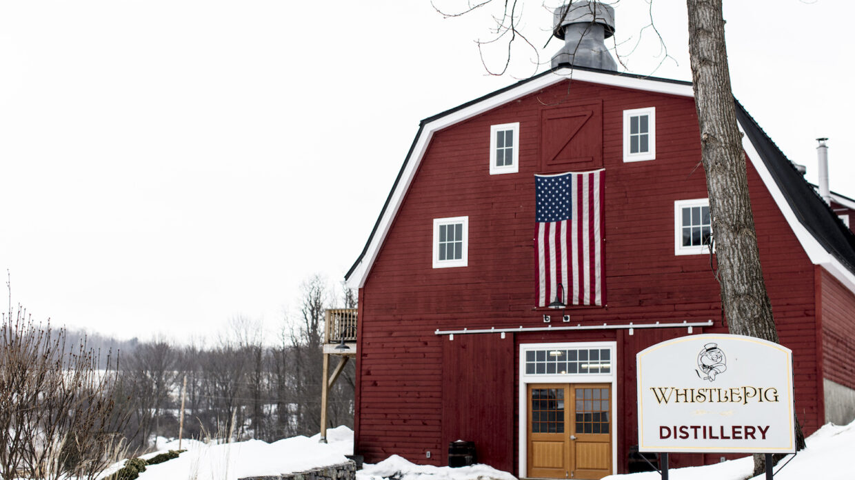 a red barn with an american flag on the exterior and the sign that reads whistlepig farm