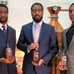 Three men stand in front of a still wearing suits, holding bottles of whiskey.