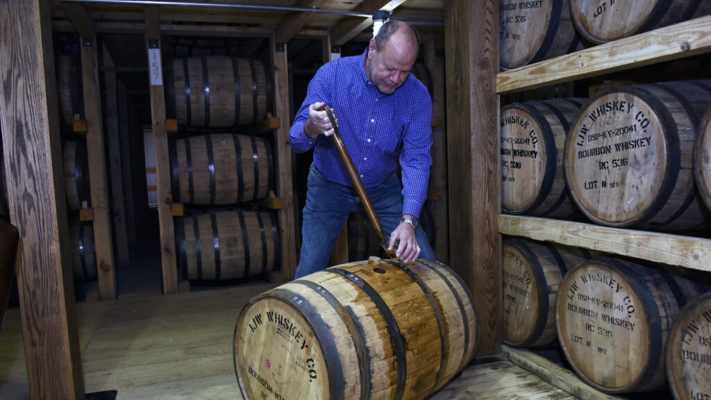 IJW master distiller Kevin Curtis pulls a sample from a barrel using a whiskey thief