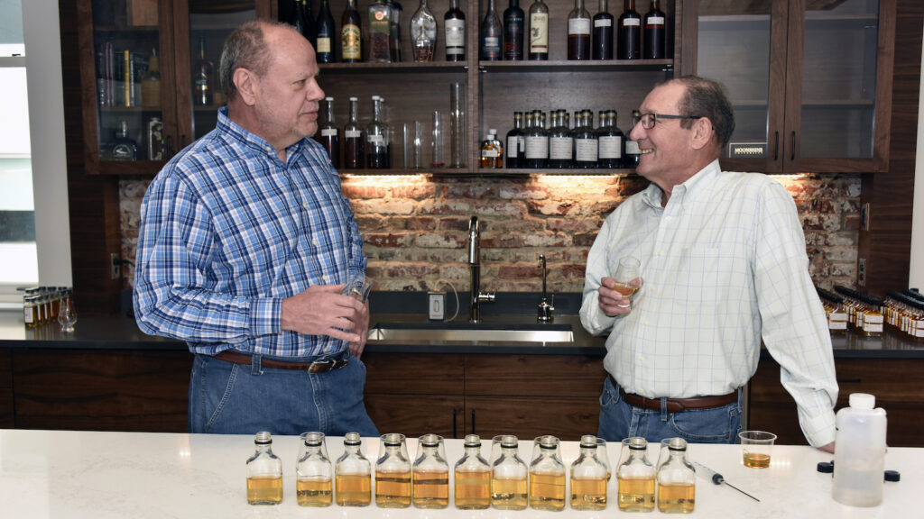 IJW master distiller Kevin Curtis and master blender Steve Hughes hold glasses of whiskey behind a table with many whiskey sample bottles