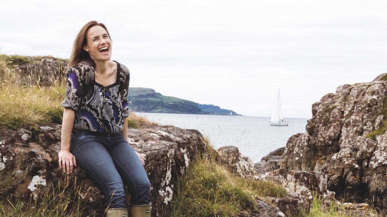 nc'nean distillery founder annabel thomas sits on a rock by the sea, smiling