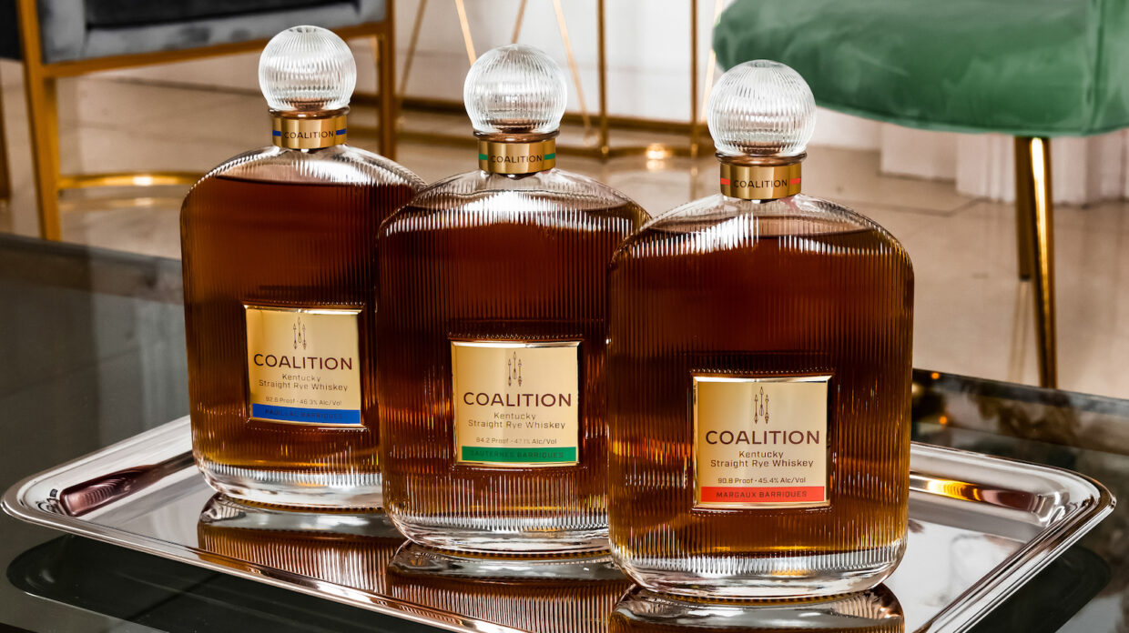 3 bottles of coalition wine cask-finished rye whisky on a mirrored tray