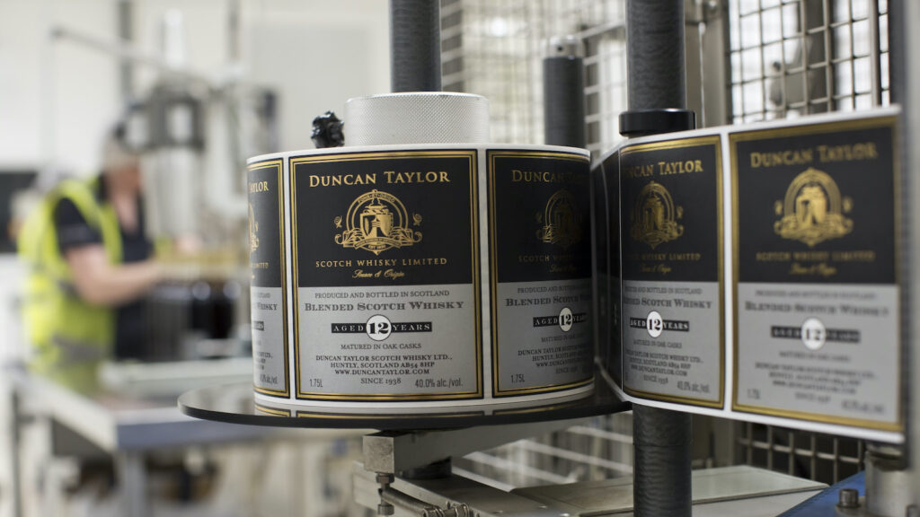 a roll of Duncan Taylor scotch whisky labels on a bottling line