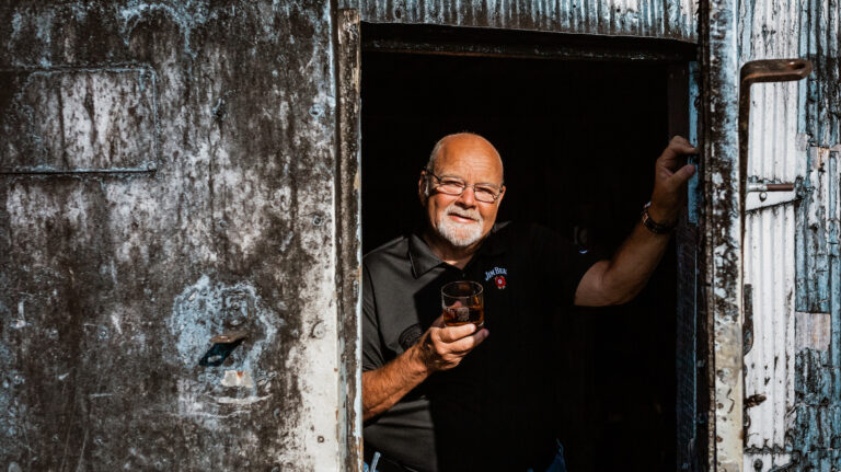 jim beam master distiller fred noe holds a rocks glass of bourbon as he steps through the open door of a rickhouse