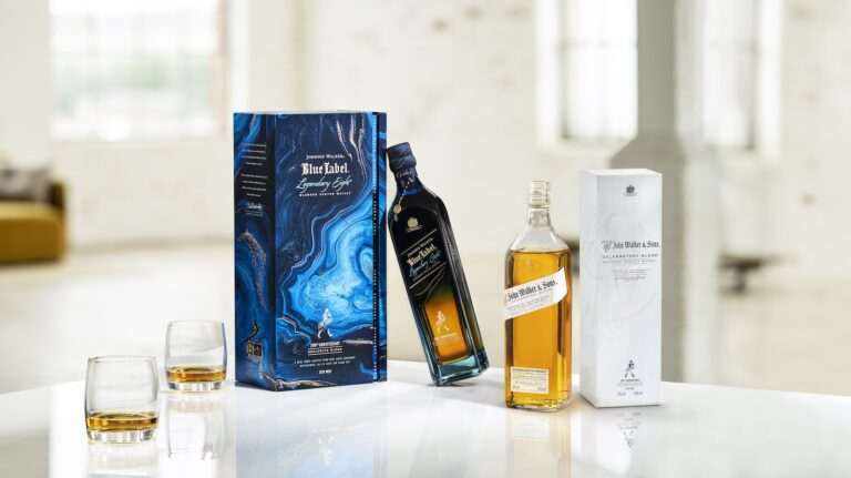 Johnnie Walker Blue Label Legendary Eight and John Walker & Sons Celebratory Blend bottles and cartons on a table with glasses of scotch