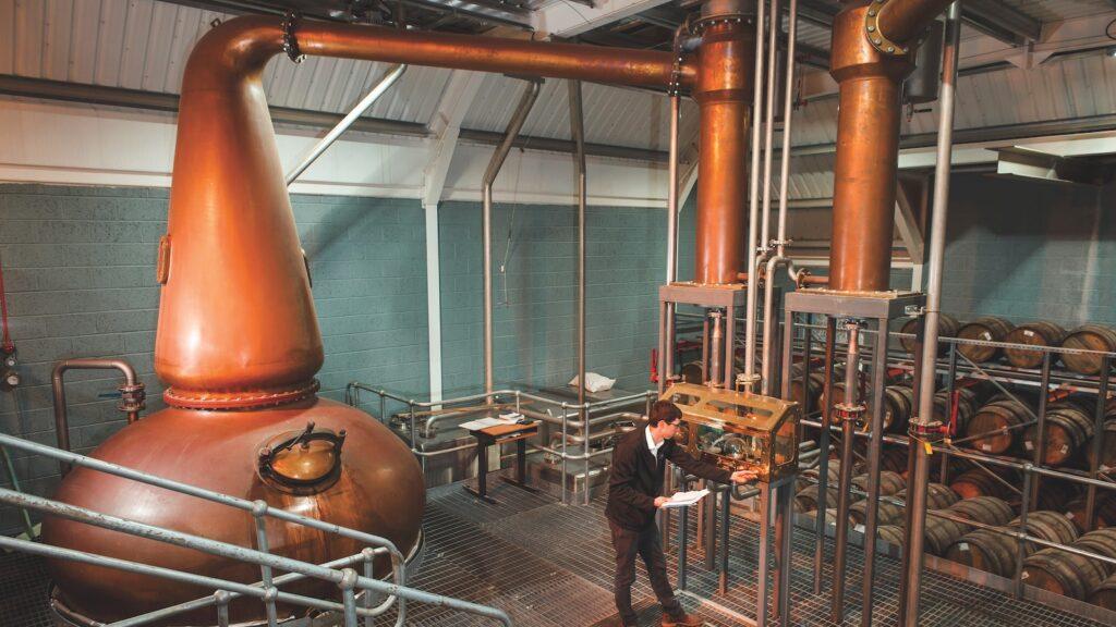 Kingsbarns distillery manager Peter Holroyd standing by the spirit safe amid copper pot stills