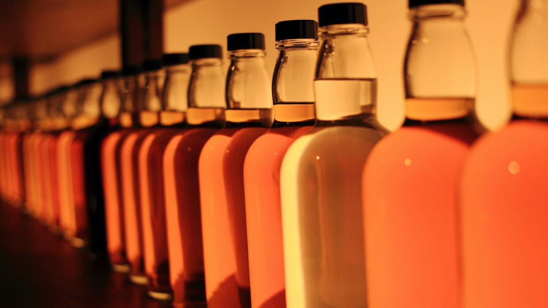Orange Whisky Bottles In Row On Table