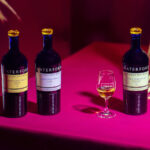 Waterford Whisky Dunmore, Dunbell, and Rathclogh bottles on a hot pink table with a stem glass of whiskey