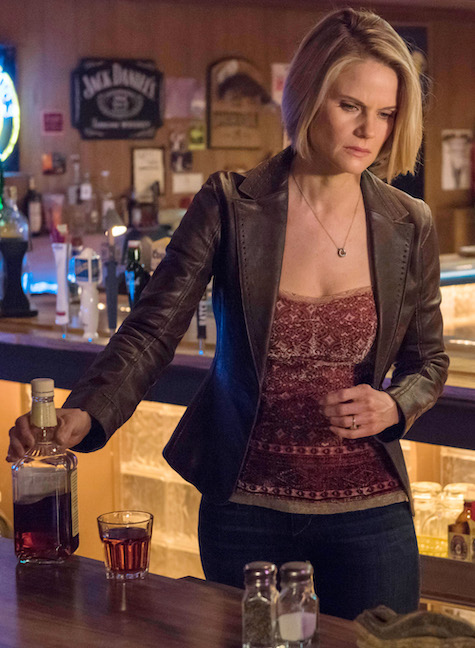 A woman stands behind a bar with a glass of whiskey.