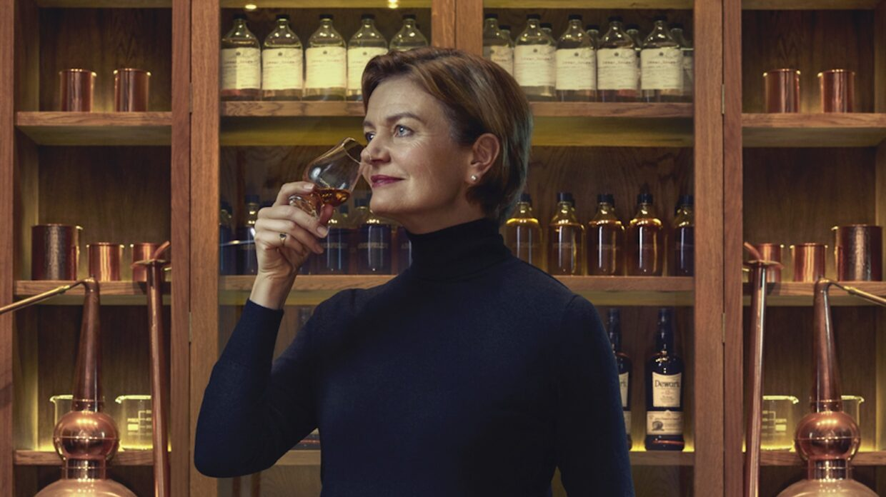 A woman noses a whiskey glass inside a blending room.