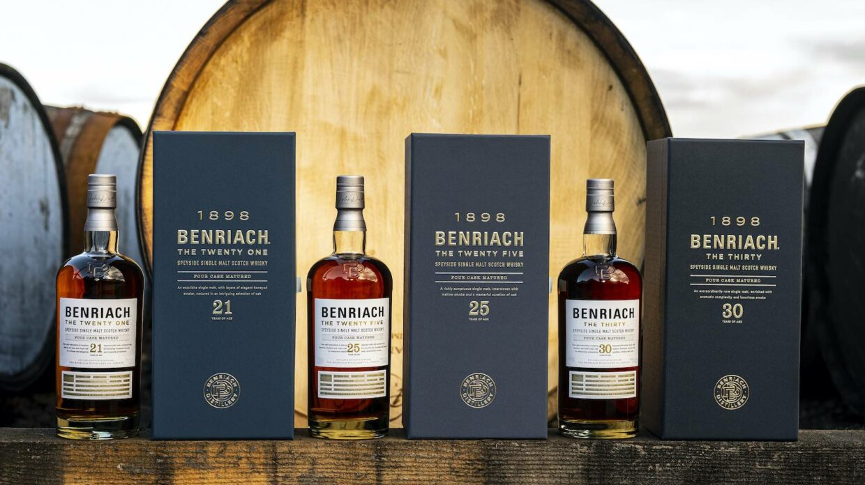 bottles and boxes of benriach the twenty one, the twenty five, and the thirty speyside single malt scotch in front of a barrel