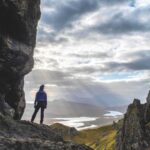 A woman stands at the base of the Old Man of Storr looking out to the Cuillin Hills on the Isle of Skye.