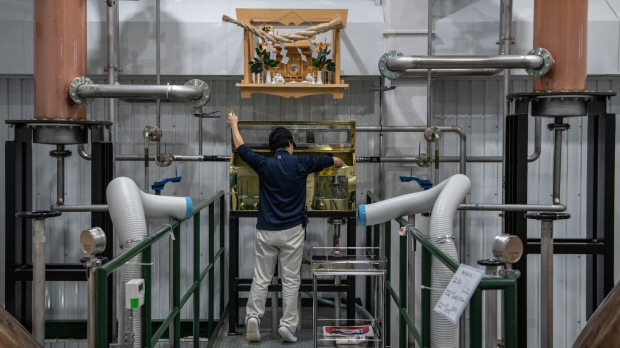 a worker at akkeshi distillery in japan checks the spirit safe beneath a shinto shrine