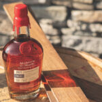 a bottle of maker's mark wood finishing series spring 2021 limited edition FAE:01 bourbon with staves on a barrel head