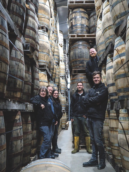 A group of people at Isle of Raasay Distillery stands amidst many barrels.