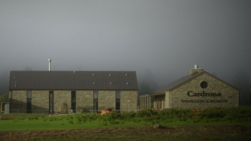 """three buildings, one reads """"Cardrona,"""" all in front of foggy background"""