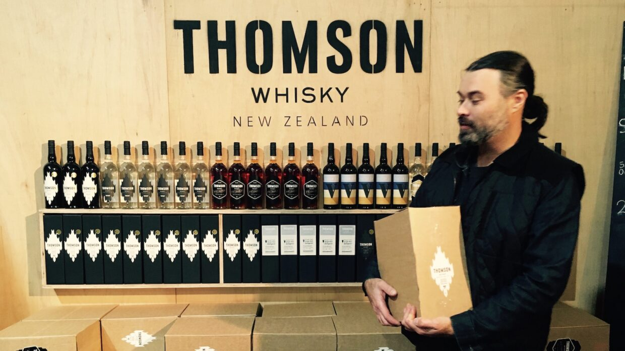 "man holding box stands in front of whisky bottles, words ""Thomson Whisky New Zealand"" on wall in background"