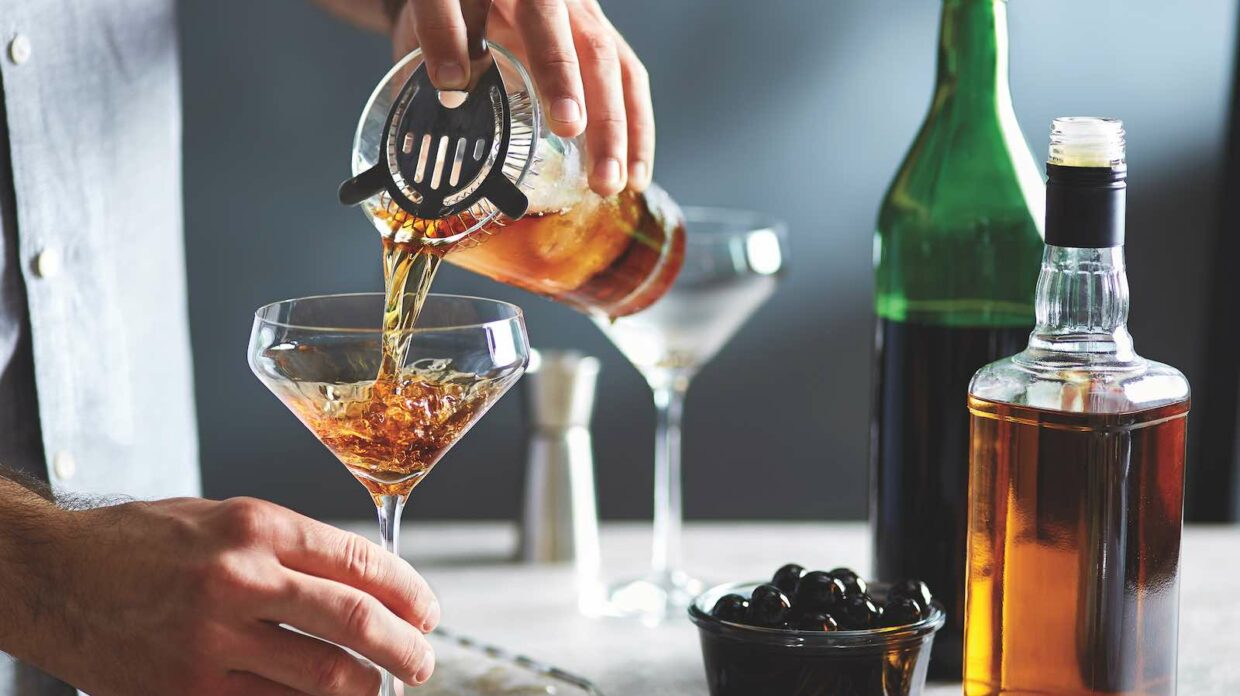 Professional bartender pouring cocktail in glass through strainer.