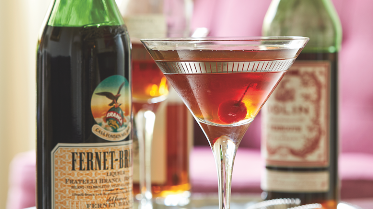 A cocktail glass with a cherry in it flanked by a bottle of Fernet