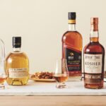 a lineup of kosher whiskies with food and glassware