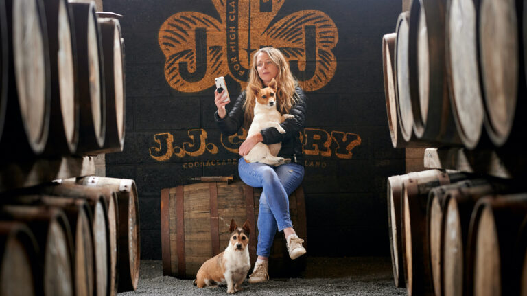 louise mcguane of J.J. Corry Irish whiskey sits among barrels with a dog in her arms and at her feet, looking at her phone