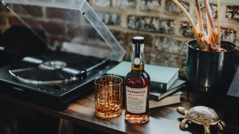 a bottle of old forester the 117 series with a glass of whiskey, a record player, and an artistic turtle