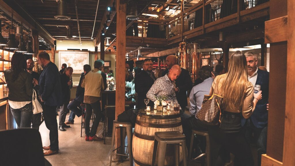 People gather in a distillery/bar space