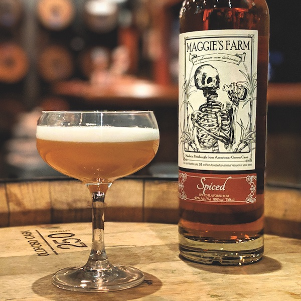 A cocktail sits on a barrel alongside a bottle of rum.
