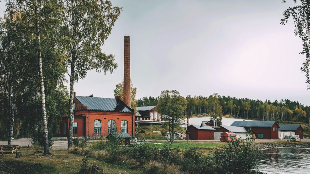the exterior of a distillery set against green foliage